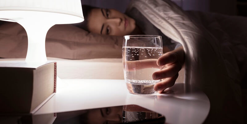 glass of water being held by woman