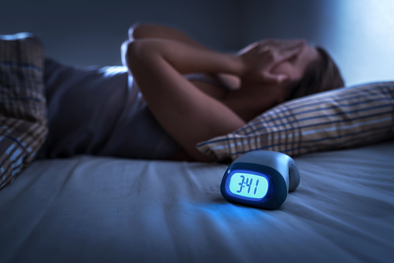 woman on bed trying to sleep