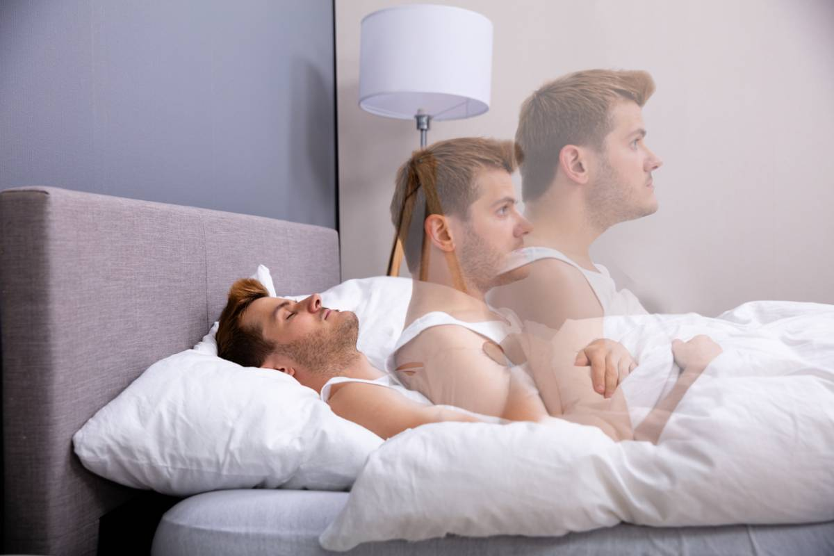 Stressed man experiencing sleep paralysis.