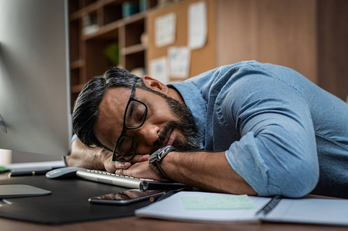 Man snoozing at work, one of the ways insomnia affects the workplace.