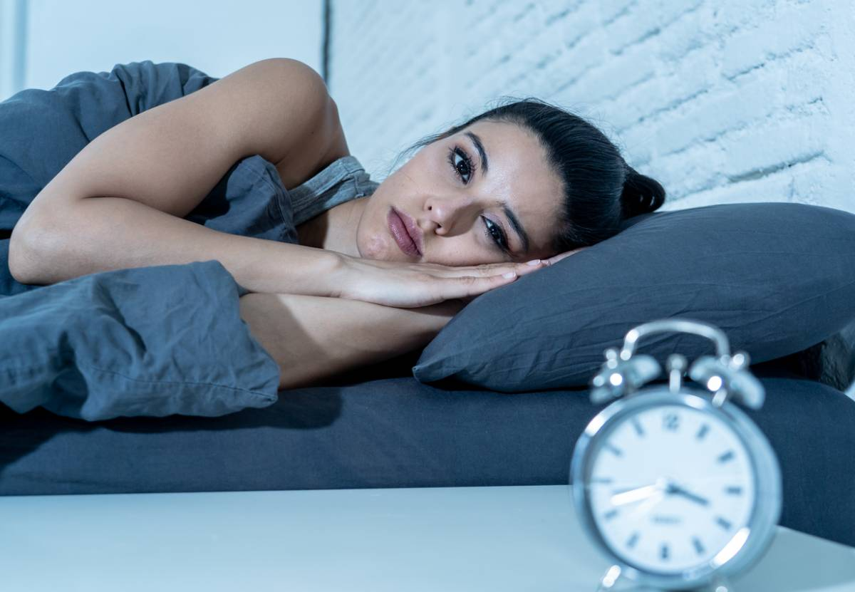 Woman awake in bed losing sleep that shortens her life.