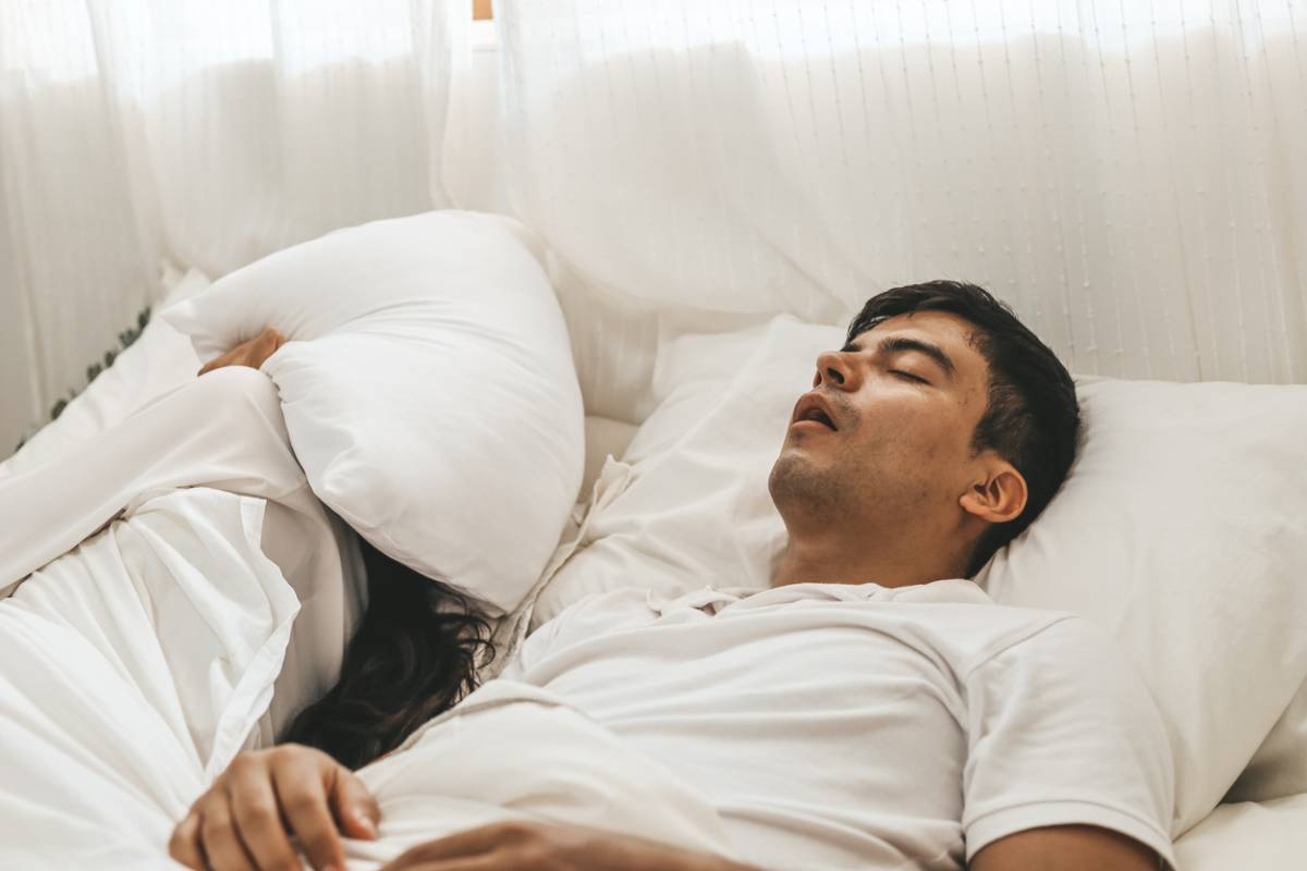 Woman wondering if snoring can be fatal as her partner snores in the bed.